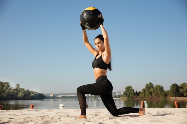 Młoda zdrowa kobieta robi rzuca się z piłką na plaży.