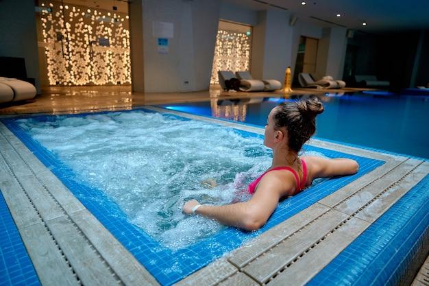 Młoda zdrowa kobieta samotnie relaks w wannie w ośrodku spa wellness.