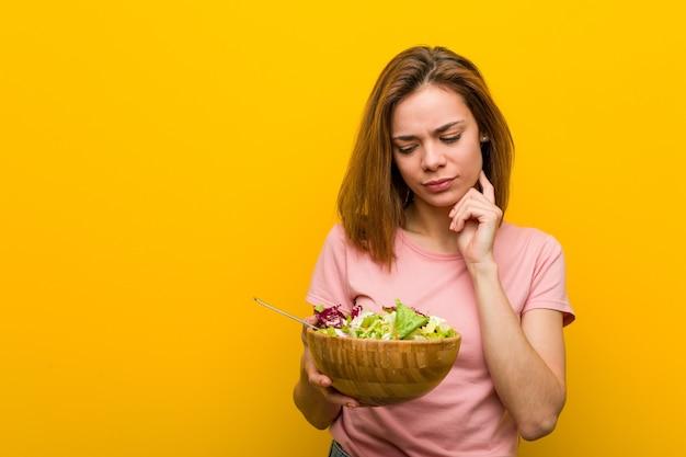Młoda zdrowa kobieta trzyma sałatkę patrząc z ukosa z wyrazem wątpliwości i sceptycyzmu.