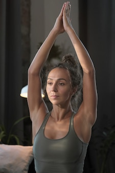 Młoda zdrowa kobieta w podkoszulku, rozciągając ramiona podczas treningu sportowego w domu