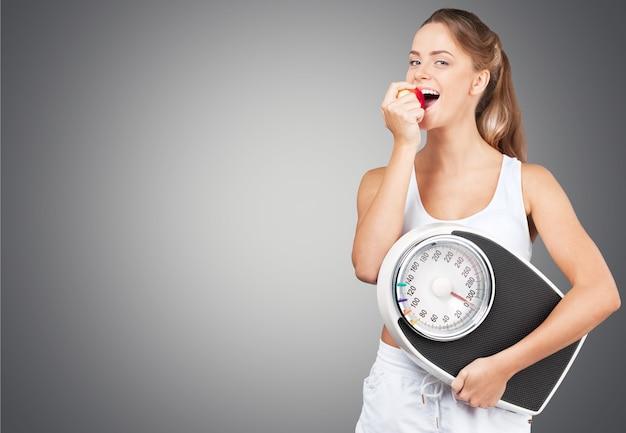 Młoda zdrowa kobieta z jabłkiem i łuskami na białym tle