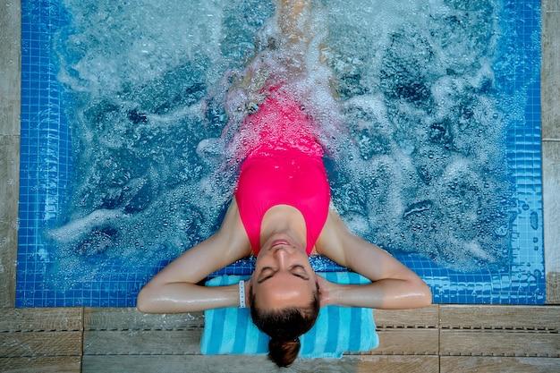 Młoda zdrowa kobieta z zamkniętymi oczami i rękami za głową, relaksując się samotnie w wannie w ośrodku spa wellness.