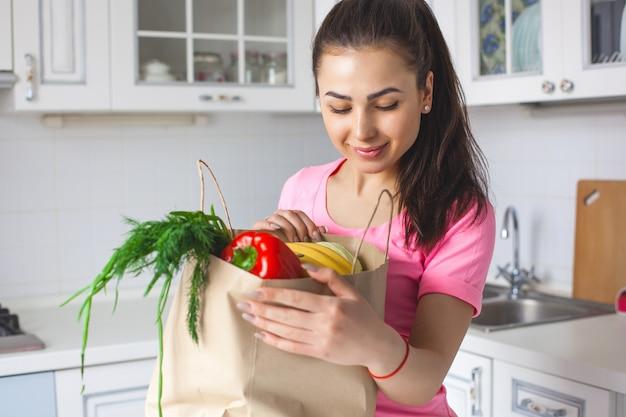 Młoda zdrowa kobieta ze świeżymi warzywami w kuchni