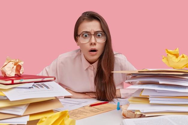 Młoda zdumiona kobieta siedzi przed stosem papierów, nosi okulary z grubymi soczewkami, formalną koszulę, czuje się przeciążona, ma dużo pracy