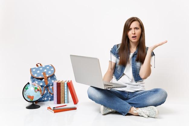 Młoda zdumiona kobieta trzyma się studenta za pomocą komputera przenośnego, rozkładając rękę siedzącą w pobliżu plecaka na świecie, izolowane podręczniki szkolne