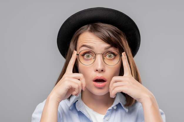 Młoda zdumiona kobieta w kapeluszu i okularach, patrząc na ciebie z wyrazem twarzy pokazującym wielkie zdumienie