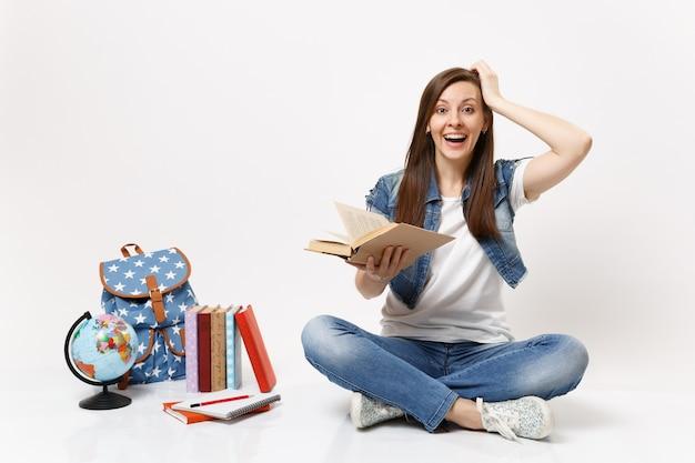 Młoda zdumiona roześmiana studentka w dżinsowych ubraniach trzyma książkę prowadzącą rękę w pobliżu głowy siedzieć w pobliżu kuli ziemskiej, plecaka, podręczników szkolnych na białym tle
