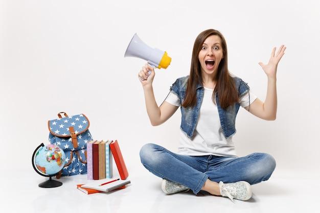 Młoda zdumiona studentka w dżinsowych ubraniach rozkładająca ręce trzymająca megafon siedzący w pobliżu globusa plecak szkolna książka na białym tle