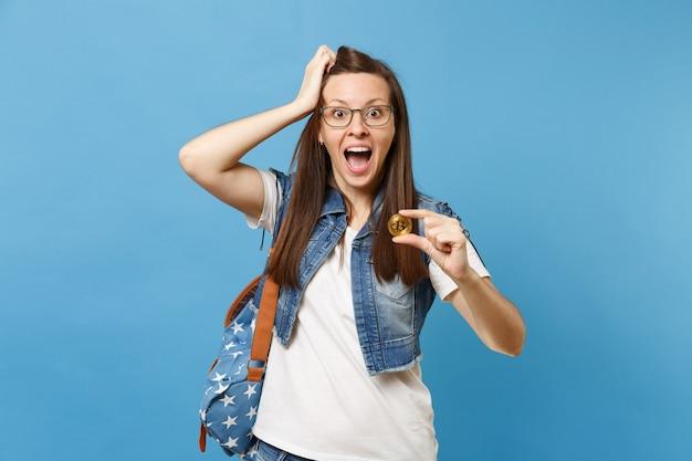 Młoda zdumiona zszokowana studentka z otwartymi ustami, trzymając się głowy trzymaj metalową monetę bitcoin o złotym kolorze na białym tle na niebieskim tle. przyszła waluta. edukacja w liceum ogólnokształcącym.