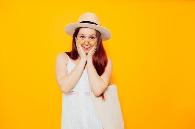 Młoda zdziwiona atrakcyjna kobieta w białym kapeluszu i białej letniej sukience z eko torby na zakupy z uśmiechem.