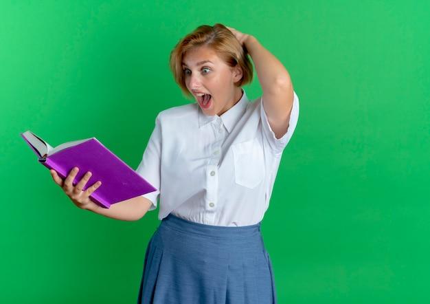 Młoda zdziwiona blondynka rosjanka kładzie rękę na głowie za patrząc na książkę