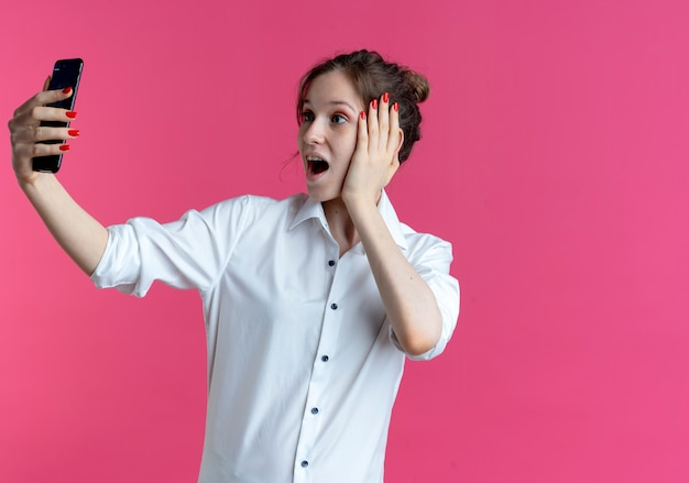 Młoda zdziwiona blondynka rosjanka kładzie rękę na twarzy patrząc na telefon