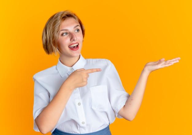 Młoda zdziwiona blondynka rosjanka wskazuje na pustą rękę