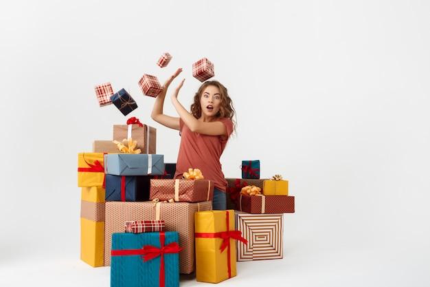 Młoda zdziwiona kędzierzawa kobieta wśród leżących i spadających pudełek prezentowych
