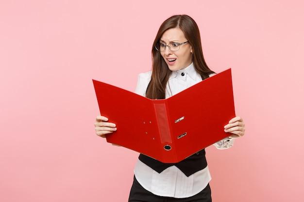 Młoda zdziwiona kobieta biznesu w garniturze, okulary patrząc na czerwony folder na dokument dokumentów na białym tle na pastelowym różowym tle. szefowa. koncepcja bogactwa kariery osiągnięcia. skopiuj miejsce na reklamę.