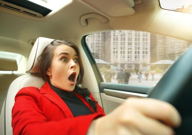 Młoda zdziwiona kobieta podczas prowadzenia samochodu