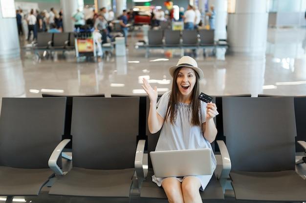 Młoda zdziwiona podróżniczka turystyczna kobieta pracująca na laptopie trzymaj karty kredytowe rozłożone ręce, czekaj w holu na międzynarodowym lotnisku