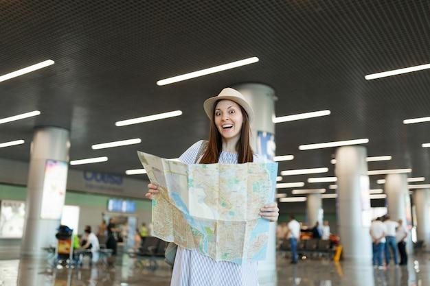 Młoda zdziwiona podróżniczka turystyczna kobieta w kapeluszu trzymająca papierową mapę, szukająca trasy i czekająca w holu na międzynarodowym lotnisku