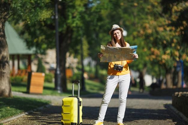 Młoda zdziwiona podróżniczka turystyczna kobieta w żółtym letnim kapeluszu na co dzień z mapą miasta walizka spacerująca po mieście na świeżym powietrzu. dziewczyna wyjeżdża za granicę na weekendowy wypad. styl życia podróży turystycznej.