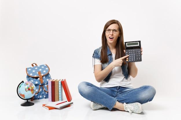 Młoda zdziwiona przypadkowa studentka wskazująca palcem wskazującym na kalkulatorze, ucząca się matematyki, siedząca w pobliżu kuli ziemskiej, plecaka, podręczników szkolnych na białym tle