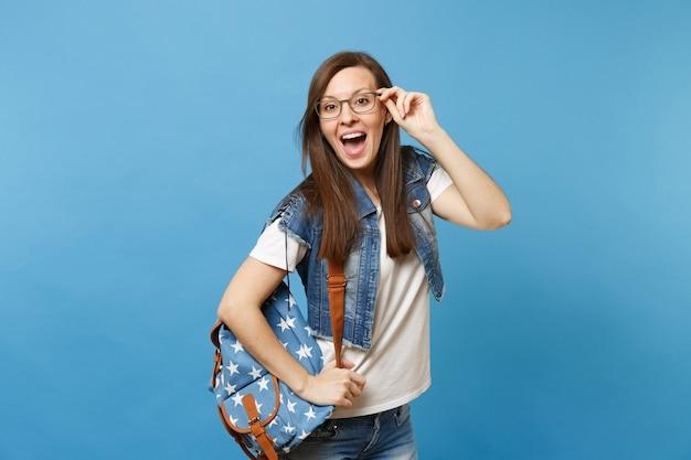 Młoda zdziwiona szczęśliwa studentka z otwartymi ustami w białej koszulce i dżinsowych ubraniach z plecakiem trzymająca okulary na białym tle na niebieskim tle. edukacja w koncepcji liceum uniwersyteckiego.