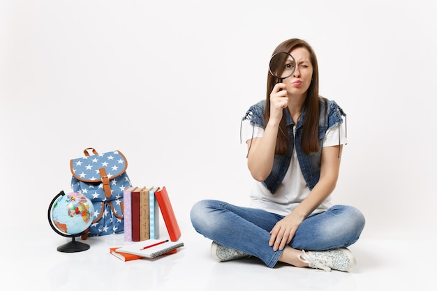 Młoda zdziwiona zainteresowana studentka trzymająca się patrząc na szkło powiększające siedząca w pobliżu kuli ziemskiej, plecaka, podręczników szkolnych na białym tle