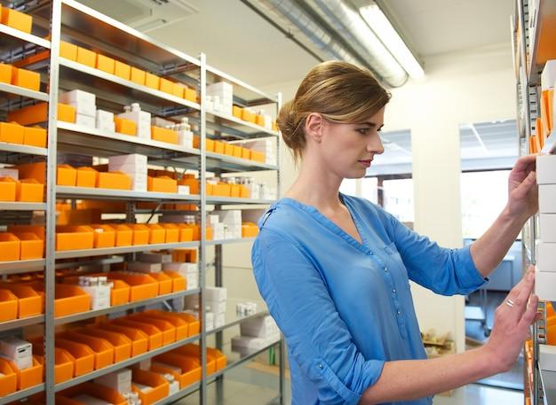 Młoda żeńska farmaceuta patrzeje dla medycyny na półkach