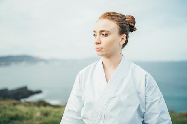 Młoda żeńska karate atleta patrzeje daleko od na górze falezy