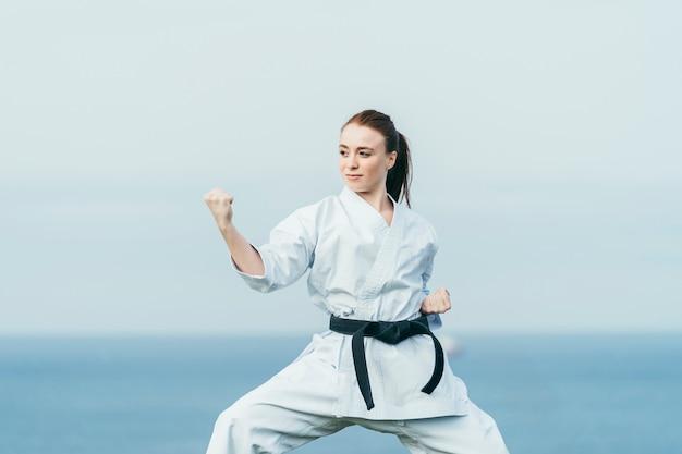 Młoda żeńska karate atleta przygotowywa atakować. ma na sobie czarny pas i białe kimono