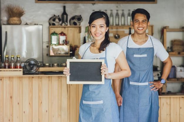 Młoda żeńska kelnerka stoi pustego blackboard znaka i trzyma przy kawiarnią