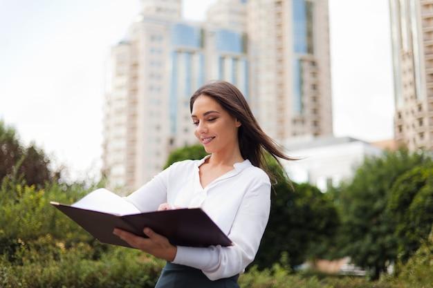 Młoda żeńska kierownik jest ubranym spódnicę i bluzkę trzyma falcówkę z dokumentami