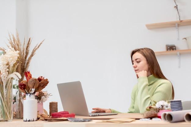 Młoda żeńska kwiaciarnia pracuje na jej laptopie