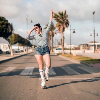 Młoda żeńska łyżwiarka z jej ręką podnosił tana na drodze