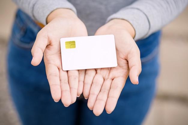 Młoda żeńska mienia pusta kredytowa karta, plenerowa