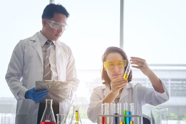 Młoda żeńska naukowiec pozycja z nauczycielem w lab pracowniku robi badaniu medycznym