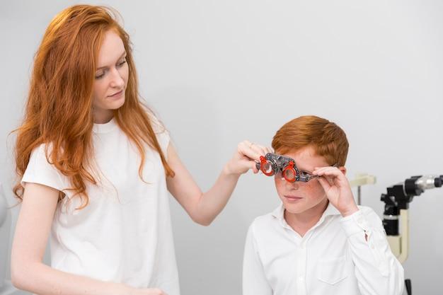 Młoda żeńska optyk jest ubranym optometrist próby ramę śliczny chłopiec dla sprawdzać jego oczy