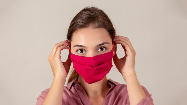 Młoda żeńska pielęgniarka stawia na czerwonej tkaniny medycznej masce podczas pandemii.