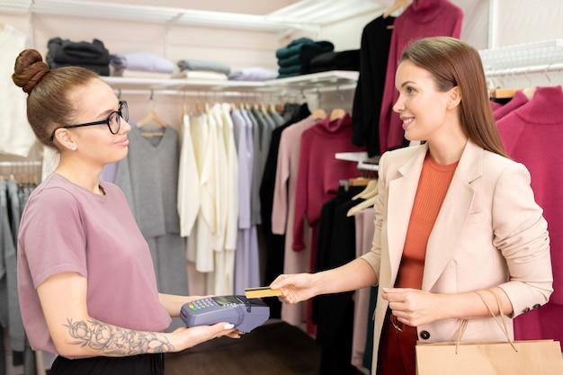 Młoda żeńska sprzedawczyni z terminalem płatniczym w rękach, patrząc na eleganckiego klienta trzymającego kartę kredytową nad maszyną w butiku