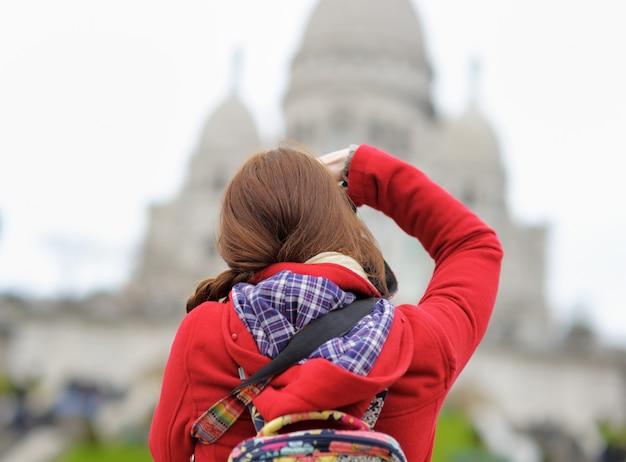 Młoda żeńska turystyczna bierze fotografia sacre-coeur katedra, paryż, francja