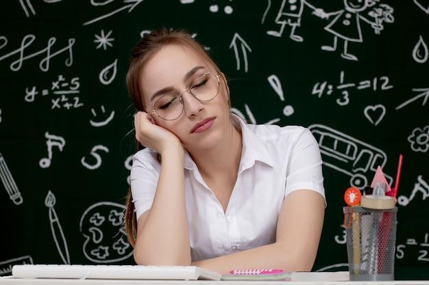 Młoda żeńskiego ucznia dosypianie w sala lekcyjnej