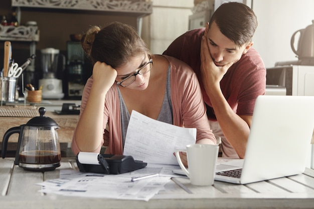 Młoda zestresowana kaukaska para w obliczu kłopotów finansowych, siedząca przy kuchennym stole z papierami, kalkulatorem i laptopem oraz czytająca dokument z banku, wyglądająca na sfrustrowaną i nieszczęśliwą