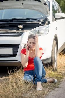 Młoda zestresowana kobieta siedzi przy zepsutym samochodzie na poboczu i rozmawia przez telefon