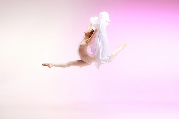 Młoda zgrabna tancerka baletowa lub klasyczne baleriny taniec w studio różowy. kaukaski model na pointach