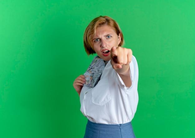 Młoda zirytowana blondynka rosjanka trzyma pieniądze i wskazuje na aparat na białym tle na zielonym tle z miejsca na kopię