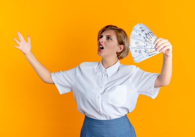 Młoda zirytowana blondynka rosjanka trzyma pieniądze, patrząc na bok z podniesioną ręką na białym tle na pomarańczowym tle z miejsca na kopię