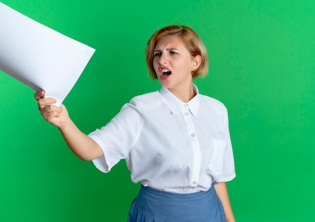 Młoda zirytowana blondynka rosjanka wyciąga arkusze papieru, patrząc na bok na białym tle na zielonym tle z miejsca na kopię