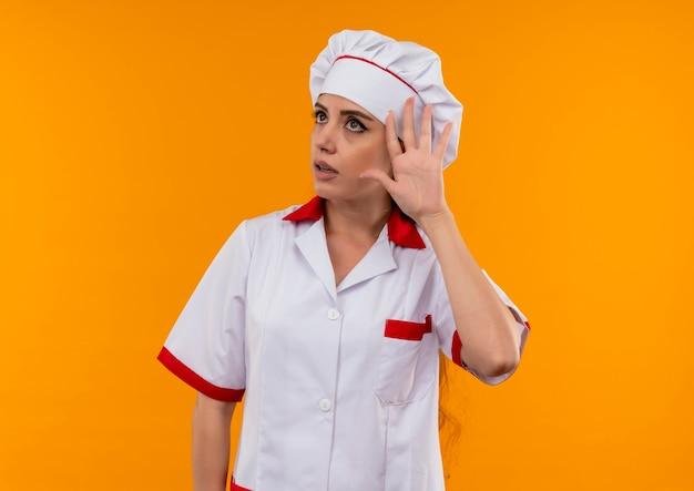 Młoda zirytowana dziewczynka kaukaski kucharz w gestach szefa kuchni nie słyszy znaku na pomarańczowym tle z miejsca na kopię