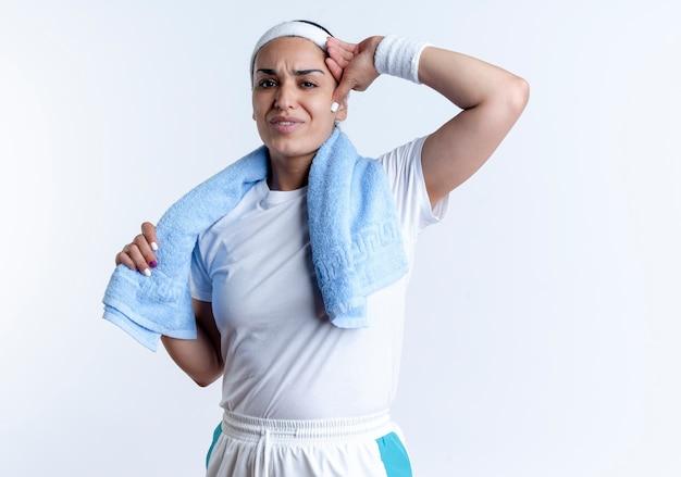 Młoda zirytowana kaukaska sportowa kobieta nosząca opaskę i opaski na rękę z ręcznikiem na szyi kładzie rękę na głowie odizolowaną na białej przestrzeni z miejscem na kopię