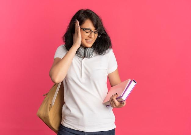 Młoda zirytowana, ładna kaukaska uczennica w okularach, tylna torba i słuchawki na szyi, zamyka ucho ręką trzymającą książkę i notatnik na różowo z miejscem na kopię