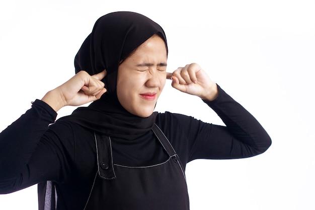 Młoda zirytowana muzułmanka wkłada palce do uszu z zamkniętymi oczami